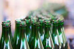 Muchas botellas en la banda transportadora Fotos de archivo libres de regalías