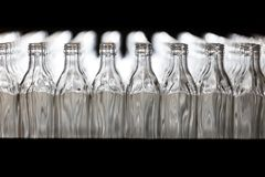 Muchas botellas en la banda transportadora en la fábrica de cristal foto de archivo