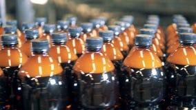 Muchas botellas plásticas con la cerveza se están moviendo a lo largo del mecanismo de transporte almacen de metraje de vídeo