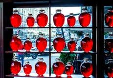 Muchas botellas redondas de diversos tamaños con el soporte líquido transparente rojo en de madera shalved contra ventana grande Imagen de archivo