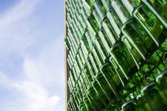 Muchas botellas vacías verdes que cuelgan en clavos con el cielo azul Imagen de archivo libre de regalías
