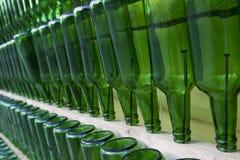 Muchas botellas vacías verdes que cuelgan en clavos Pare el alcoholismo concentrado Imagenes de archivo