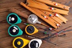 Muchas cañas de pescar para la pesca del invierno en un b de madera natural marrón Fotografía de archivo libre de regalías