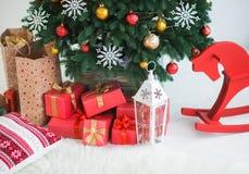 Muchas cajas envueltas en papel festivo rojo bajo ramas del pino Fotografía de archivo libre de regalías