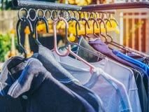 Muchas camisas que cuelgan en cuerda para tender la ropa foto de archivo