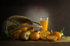 Muchas clases de frutas en a en cesta de mimbre y zumo de naranja encendido Imagen de archivo libre de regalías