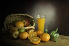 Muchas clases de frutas en a en cesta de mimbre y zumo de naranja encendido Imagenes de archivo