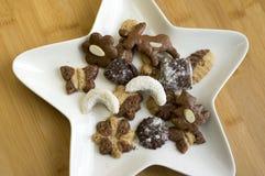 Muchas clases de galletas de la Navidad en la placa blanca de la estrella imagen de archivo