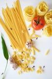 Muchas clases de pastas y de verduras en el fondo blanco foto de archivo