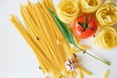Muchas clases de pastas y de verduras en el fondo blanco imagen de archivo