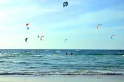 Muchas cometas en el mar embarque de la tabla hawaiana en la playa Equilibre, los deportes extremos, resto del grupo, intereses c fotos de archivo libres de regalías