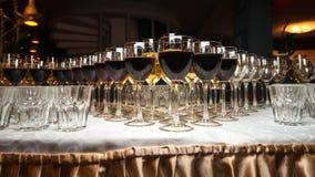Muchas copas con el vino y el champán en la tabla hermosa Imagenes de archivo