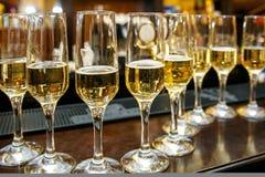Muchas copas de vino con un champán delicioso fresco o un vino blanco Imagen de archivo libre de regalías