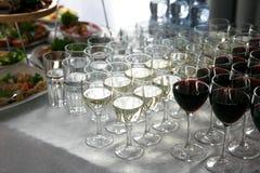 Muchas copas de vino con un vino delicioso, blanco y rojo fresco en el abastecimiento del evento Imagen de archivo
