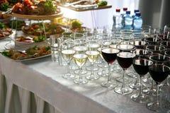 Muchas copas de vino con un vino delicioso, blanco y rojo fresco en el abastecimiento del evento Fotos de archivo libres de regalías