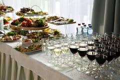 Muchas copas de vino con un vino delicioso, blanco y rojo fresco en el abastecimiento del evento Foto de archivo libre de regalías
