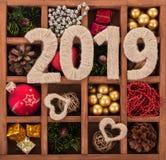 Muchas decoraciones de la Navidad, pequeños regalos y números 2019, en caja de madera con las células Fotos de archivo
