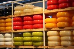 Muchas diversas formas del queso de Holanda coloreado apilado en estantes aseados producto culinario típico de Amsterdam fotografía de archivo
