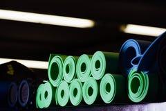 Muchas esteras de la yoga verdes y colores azules encendido Fotografía de archivo libre de regalías