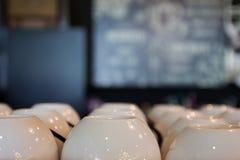 Muchas filas de la pila pura limpia de las tazas del café con leche fijaron en la tabla en Foto de archivo libre de regalías