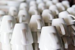Muchas filas de las tazas puras del café con leche Fotos de archivo