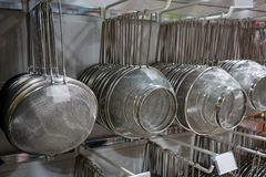 Muchas filas de los coladores y de los tamices del metal plateado que cuelgan en encontrado Fotos de archivo