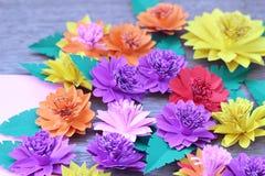 Muchas flores de papel coloridas en un fondo con un surfac liso Fotografía de archivo libre de regalías