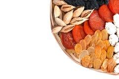 Muchas frutas secadas en una placa de madera redonda, los anacardos, las pasas, los higos, la pasa y los albaricoques aislados en fotografía de archivo