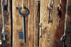 Muchas llaves que cuelgan en una secuencia Fondo de madera Foco selectivo Foto de archivo