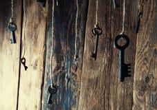 Muchas llaves que cuelgan en una secuencia Fondo de madera Foco selectivo Imagen de archivo