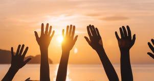 Muchas manos aumentadas contra el cielo de la puesta del sol Imagen de archivo libre de regalías
