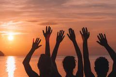 Muchas manos aumentadas contra el cielo de la puesta del sol Fotos de archivo libres de regalías