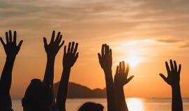 Muchas manos aumentadas contra el cielo de la puesta del sol Foto de archivo libre de regalías