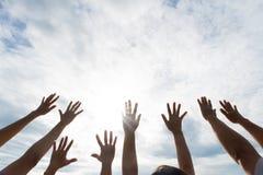 Muchas manos aumentaron para arriba contra el cielo azul Amistad imágenes de archivo libres de regalías