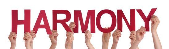 Muchas manos de la gente llevan a cabo armonía recta roja de la palabra Foto de archivo libre de regalías