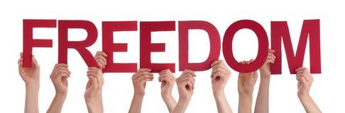 Muchas manos de la gente llevan a cabo la libertad recta roja de la palabra Imagen de archivo