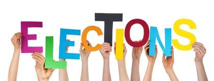 Muchas manos de la gente que celebran elecciones coloridas de la palabra Imagenes de archivo