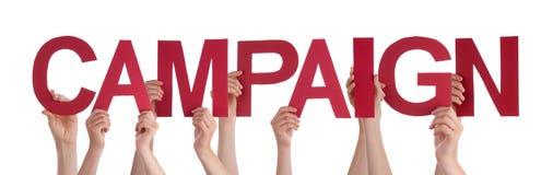 Muchas manos de la gente que llevan a cabo campaña recta roja de la palabra fotografía de archivo libre de regalías