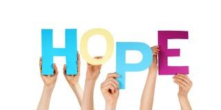 Muchas manos de la gente que llevan a cabo esperanza colorida de la palabra Imagen de archivo
