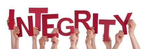 Muchas manos de la gente que llevan a cabo integridad roja de la palabra Imágenes de archivo libres de regalías