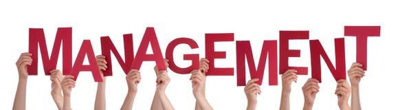 Muchas manos de la gente que llevan a cabo a la gestión roja de la palabra Imagen de archivo libre de regalías