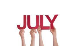 Muchas manos de la gente que llevan a cabo la palabra recta roja julio Imagen de archivo