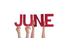 Muchas manos de la gente que llevan a cabo la palabra recta roja junio Imagenes de archivo