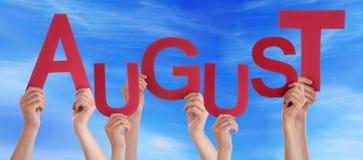Muchas manos de la gente que llevan a cabo la palabra roja August Blue Sky Fotos de archivo