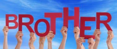 Muchas manos de la gente que llevan a cabo la palabra roja Brother Blue Sky Fotografía de archivo