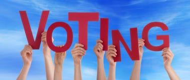 Muchas manos de la gente que llevan a cabo la palabra roja que vota el cielo azul Fotos de archivo