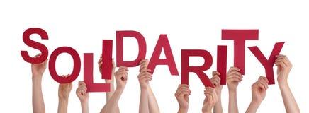 Muchas manos de la gente que llevan a cabo solidaridad roja de la palabra Fotos de archivo libres de regalías