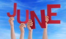 Muchas manos de la gente que sostienen el cielo azul de junio de la palabra roja Fotos de archivo libres de regalías