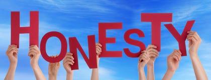 Muchas manos de la gente que sostienen el cielo azul de la honradez roja de la palabra Foto de archivo libre de regalías