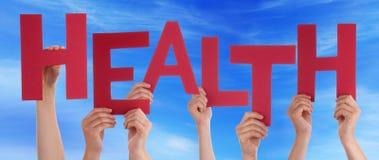 Muchas manos de la gente que sostienen el cielo azul de la salud roja de la palabra foto de archivo